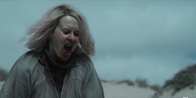 Sarah Paulson as TB Karen stands on the beach with her mouth open covered in blood