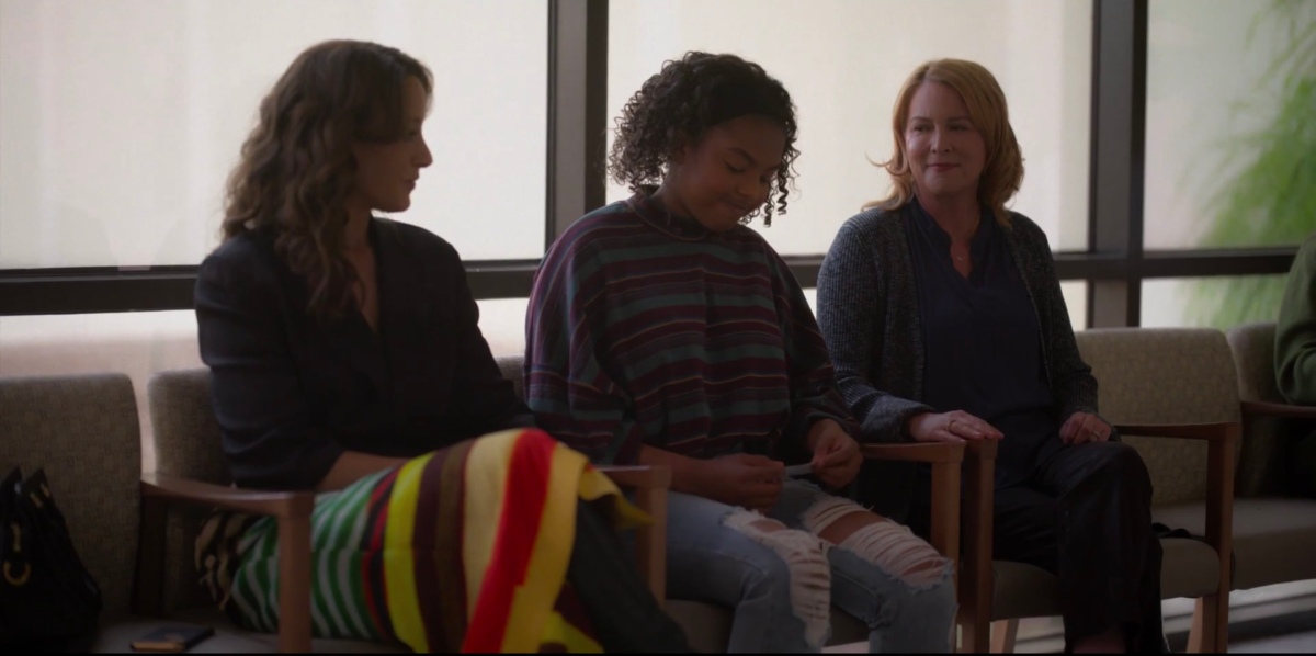 Angie staring at her lap while her Moms stare at her in the hospital waiting room
