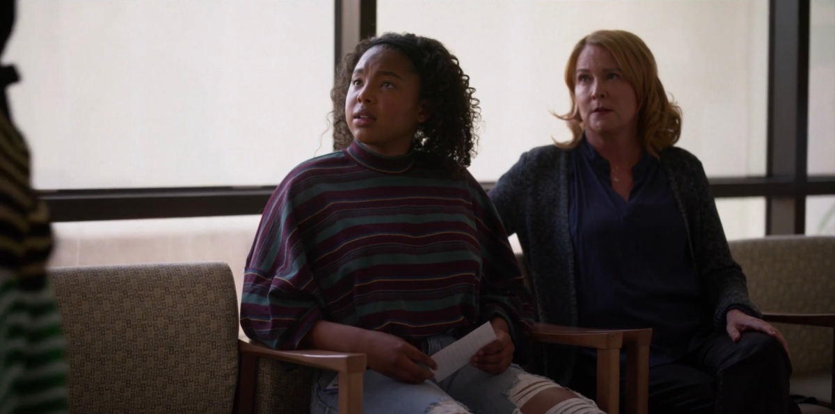 Angie looking up at Bette, sitting next to Tina