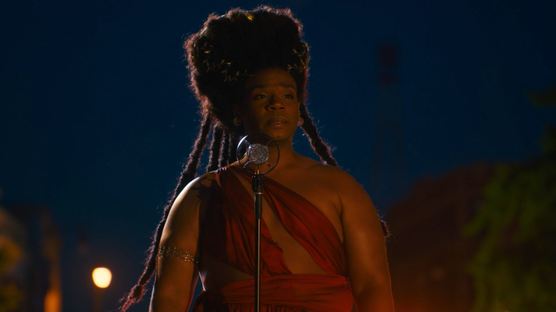 Armand Fields as King standing at a microphone in a dream sequence wearing a red dress