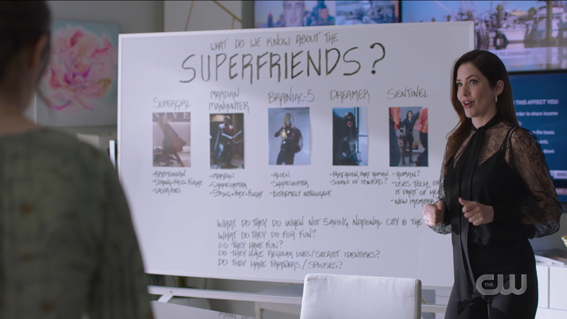 Andrea stands in front of her Superfriends whiteboard