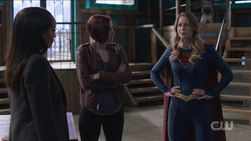 Supergirl 609: Alex stands with her arms crossed, Supergirl stands with her hands on her hips