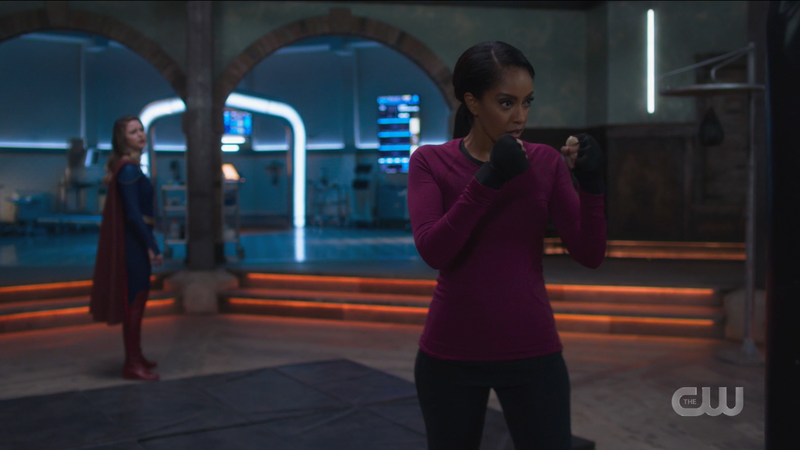 Kelly gets ready to punch a punching bag while Supergirl asks to join