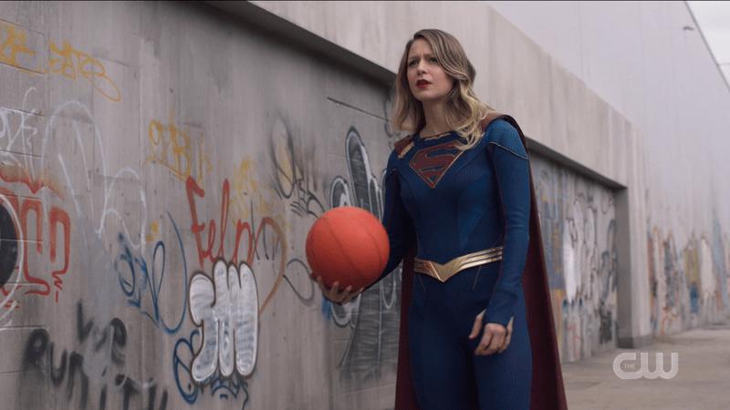 Supergirl holds a basketball like a regular Lakehawks player