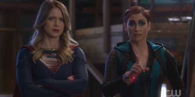 Supergirl 611: Kara with her arms crossed, Alex pointing a figure, both expressions look curious but a little concerned