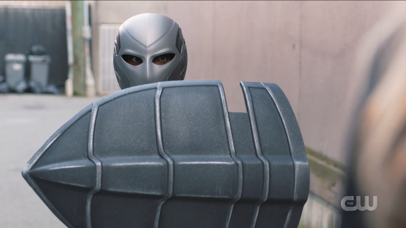 Kelly in the old guardian suit, obscured face, bulky looking