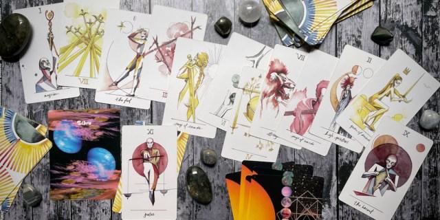 an assortment of tarot cards from the vindur deck, along with crystals