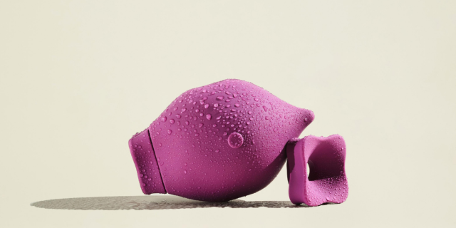 The Poet, a magenta suction sex toy shaped like a tear drop, is against an off-white background. It rests against its detachable suction mouth piece. The toy is slightly wet.