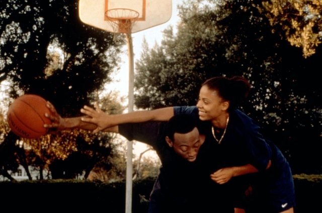 In a still from Love and Basketball, Sanaa Lathan and Omar Epps smile and play basketball.