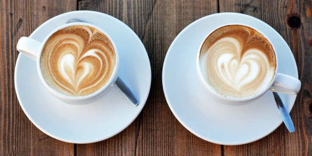 Two white coffee cups are on white plates with spoons. Each cup features latte art of a heart.
