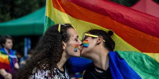 Two femme queers kiss in front of the pride flag while also having rainbow hearts painted on their faces