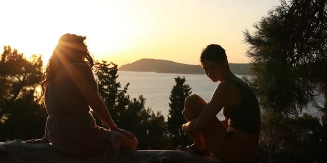 Selen Uçer as Reyhan and Ece Dizdar as Eren sit by the water as the sun sets