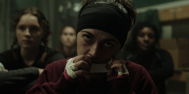 Isabelle Fuhrman as Alex Dall tears a piece of athletic tape with her teeth.