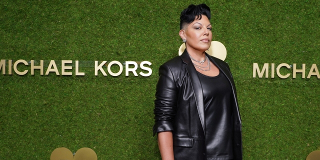 Sara Ramirez in a leather jacket against a green grass wall