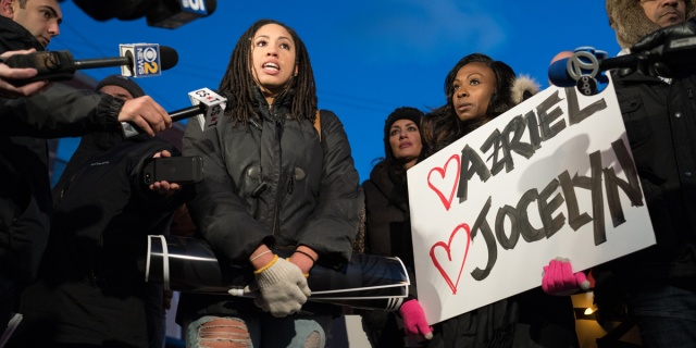 """A group of protestors stand outside R. Kelly's hearing, a black woman speaks into a microphone as another black woman holds a sign that says """"Ariel and Jocelyn, two of R Kelly's victims, with hearts around them"""""""