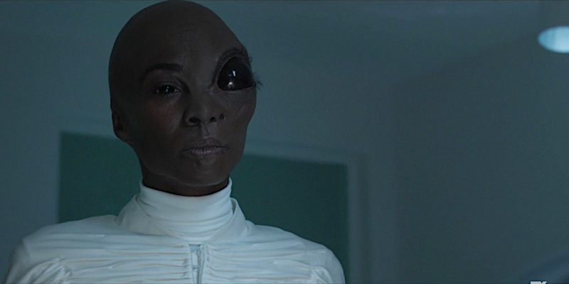 Angelica Ross as a half human half alien. She's wearing a futuristic white robe, has a giant head, and one of her eyes is giant and black.