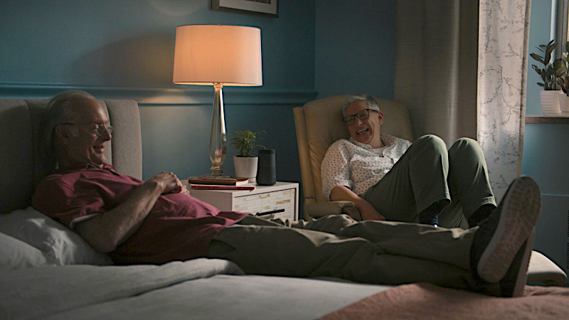 Abby sits in a chair next to her dad who is lying on a bed. They are both laughing.