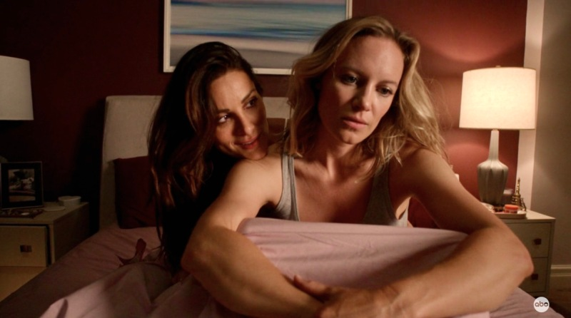 Maya is worried and Carina holds her by the waist while the couple sits up in bed on Station 19