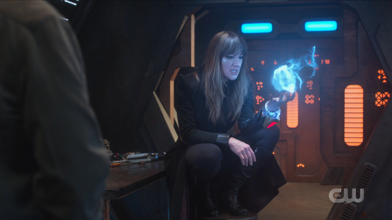 Supergirl recap 615: Nyxly sits gayly on a chair and looks at her magic ball of energy