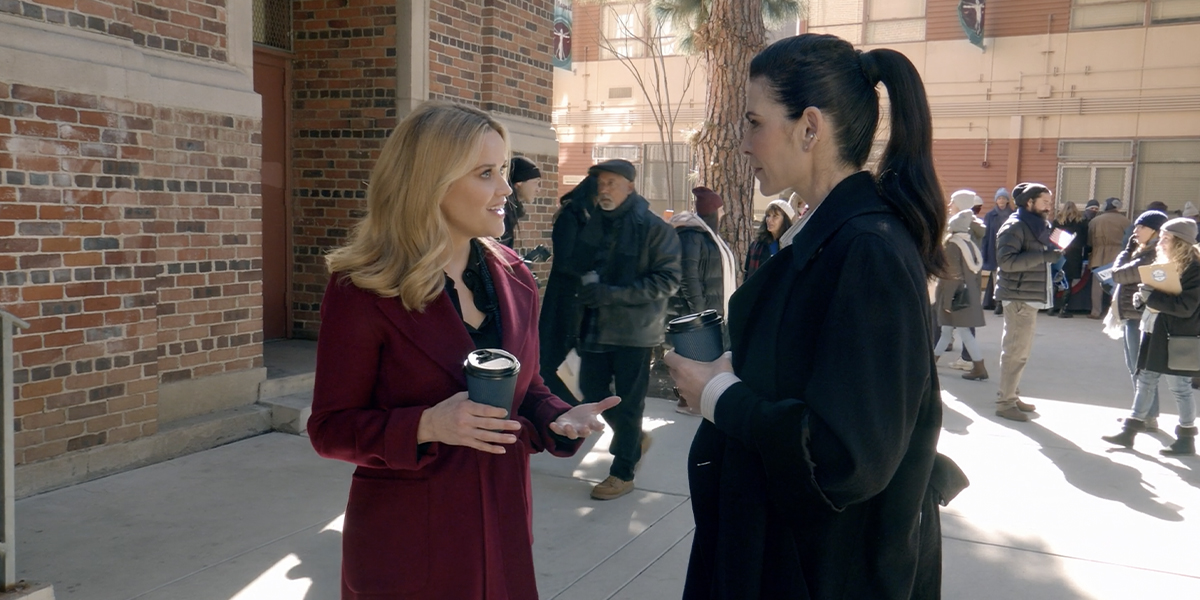 Reese Witherspoon and Juliana Margulies in The Morning Show, holding coffee cups and wearing great jackets.
