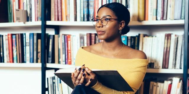 reading, against bookshelves