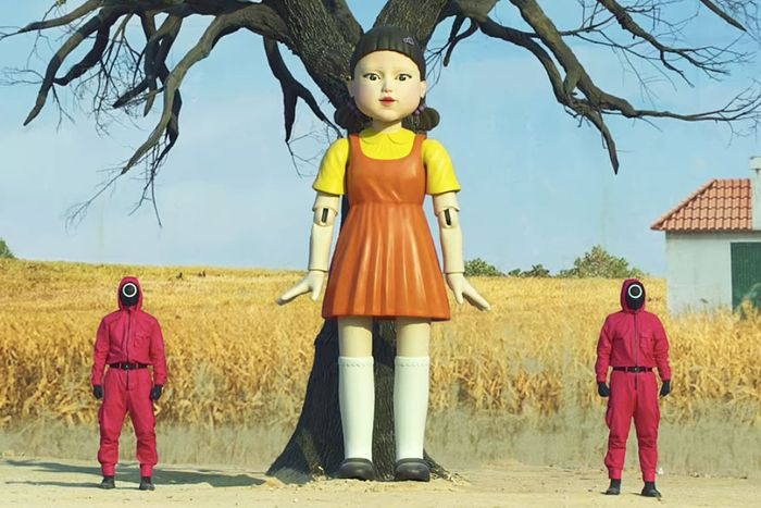 The giant Squid Game doll standing against a tree